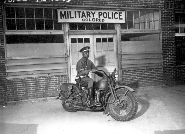 An MP on motorcycle stands ready to answer all calls around his area. Columbus, Georgia. April 13, 1942. Pfc. Victor Tampone. 111-SC-134951.