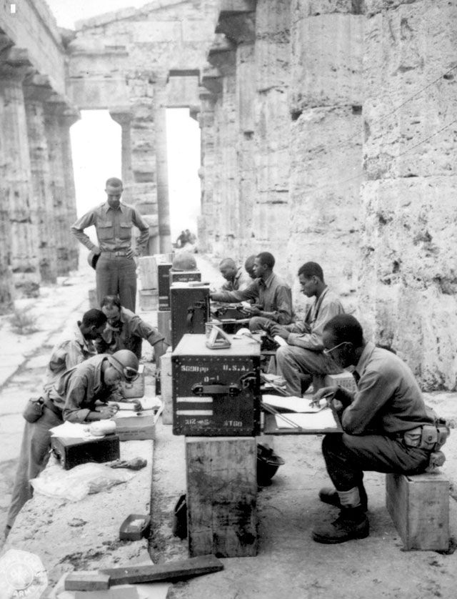 A company of men has set up its office between the columns (Doric) of an ancient Greek temple of Neptune, built about 700 B.C. At desk, front to rear: Sgts. James Shellman, Gilbert A. Terry, John W. Phoenix, Curtis A. Richardson, and Leslie B. Wood. In front of desk, front to rear: T/Sgt. Gordon A. Scott, M/Sgt. Walter C. Jackson, Sgt. David D. Jones, and WO Carlyle M. Tucker. Italy. September 22, 1943. 111-SC-181588.