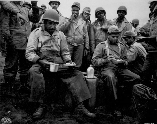 A kitchen was set up along the beach for the labor battalion unloading the boats. This picture shows a couple of the men enjoying a hot meal for a change. Massacre Bay, Attu, Aleutian Islands. May 20, 1943. T/5 Vincent A. Wallace. 111-SC-174129
