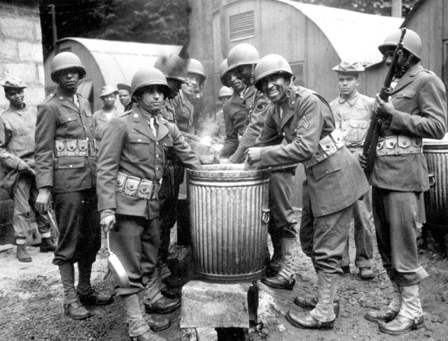 Negro soldiers draw rations at the camp cook house at their station in Northern Ireland. Detachments of Negro troops were among the latest arrivals with the American forces in Northern Ireland. Ca. August 1942. Acme. 208-AA-46G-1