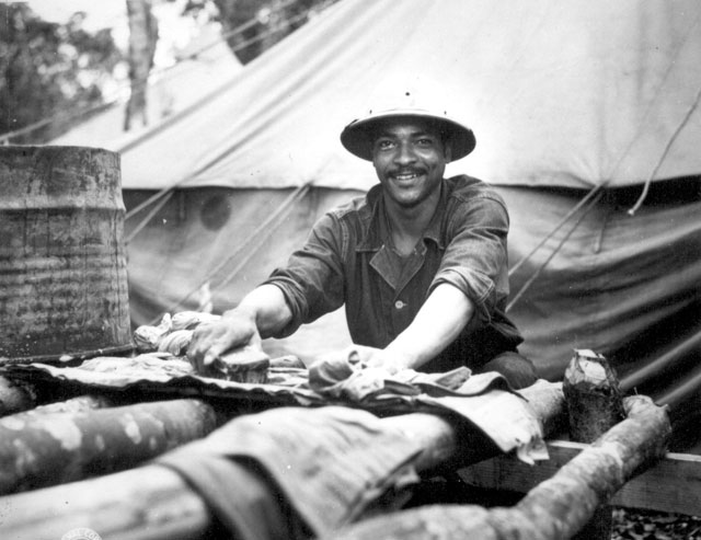 American Army Engineer task force in Liberia find themselves in a land from which their ancestors came. Wash day and Pvt. Jack David scrubs out his things on top of a table made from native trees. Ca. July 1942. Fred Morgan. 111-SC-150980-B