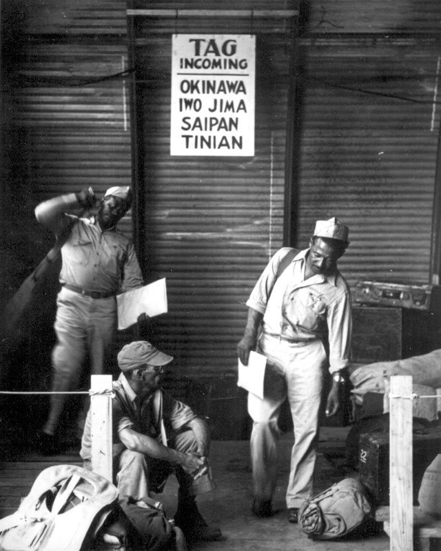 Two soldiers gather up their baggage as transportation arrives to take them to their outfit on Guam. Another soldier sits disconsolately awaiting further orders of transportation. August 4, 1945. 208-AA-63HH-1