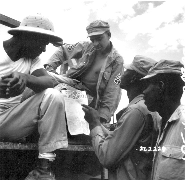 Troops in Burma stop work briefly to read President Truman's Proclamation of Victory in Europe. May 9, 1945. S/Sgt. Yarnell. 111-SC-262229