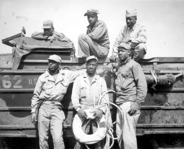Seeking to rescue a Marine who was drowning in the surf at Iwo Jima, this sextet of Negro soldiers narrowly missed death themselves when their amphibian truck was swamped by heavy seas. From left to right, back row, they are T/5 L. C. Carter, Jr., Private John Bonner, Jr., Staff Sergeant Charles R. Johnson. Standing, from left to right, are T/5 A. B. Randle, T/5 Homer H. Gaines, and Private Willie Tellie. March 11, 1945. S/Sgt. W. H. Feen. 127-N-114329