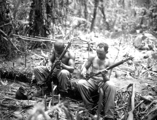 Sgt. John C. Clark and S/Sgt. Ford M. Shaw (left to right) clean their rifles in bivouac area alongside the East West Trail, Bougainville. They are members of Co. E, 25th Combat Team, 93rd Division  April 4, 1944. Lt. Schuman. 111-SC-364565