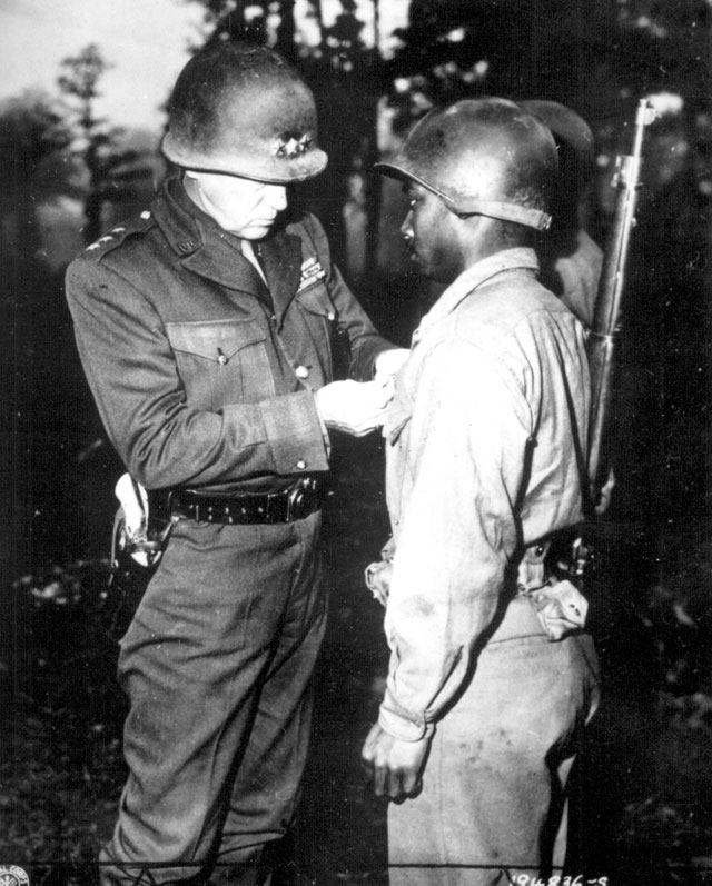 Lt. Gen. George S. Patton, U.S. Third Army commander, pins the Silver Star on Private Ernest A. Jenkins of New York City for his conspicuous gallantry in the liberation of Chateaudun, France  October 13, 1944. 208-FS-3489-2.