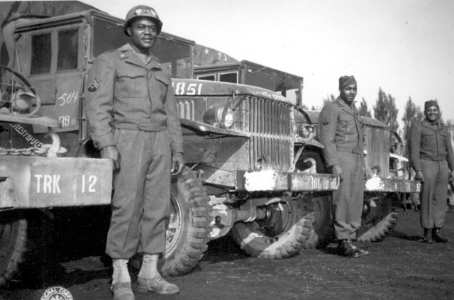 These drivers of the 666th Quartermaster Truck Company, 82nd Airborne Division, who chalked up 20,000 miles each without an accident, since arriving in the European Theater of Operations. Left to right: T/5 Sherman Hughes, T/5 Hudson Murphy, Pfc. Zacariah Gibbs. Ca. May 1945. 208-AA-32P-3