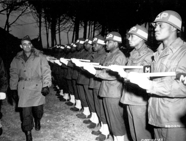 Lt. Gen. Joseph T. McNarney, Deputy Supreme Allied Commander, Mediterranean Theater, inspects Honor Guard of MPs during his tour of the Fifth Army front at the 92nd Division Sector. January 4, 1945. Yaskell. 111-SC-380271.