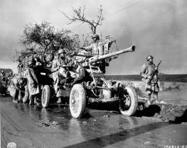 Members of Battery A, 4520 AA stand by and check their equipment while the convoy takes a break. November 9, 1944. Musae. 111-SC-196212-S.
