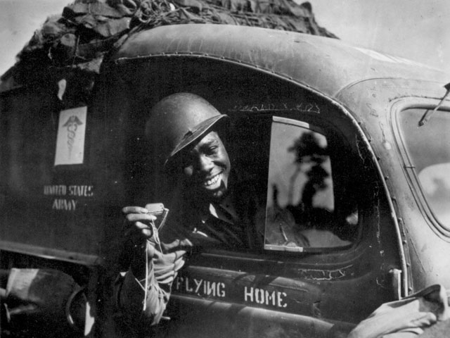 Pvt. William A. Reynolds , an ambulance driver exhibits a .50-caliber machine gun bullet which lodged above the windshield of his vehicle when he was strafed by a German plane while driving at the front in France 1944.  208-AA-32P-18.