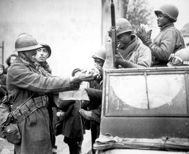 Two smiling French soldiers fill the hands of American soldiers with candy, in Rouffach, France, after the closing of the Colmar pocket. February 5, 1945. Todd. 111-SC-199861-S.