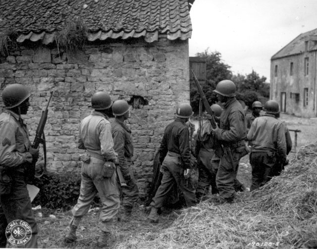 A platoon of Negro troops surrounds a farm house in a town in France, as they prepare to eliminate a German sniper holding up an advance. Omaha Beachhead, near Vierville-sur-Mer, France. June 10, 1944. Todd. 111-SC-190120.