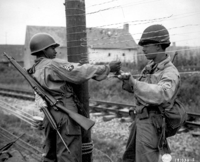 T/5 Dexter Clayton and M/Sgt. Nelson T. Ewing are tying wire to pole after sag is taken up. France. July 25, 1944. Gallo. 111-SC-191834-S.