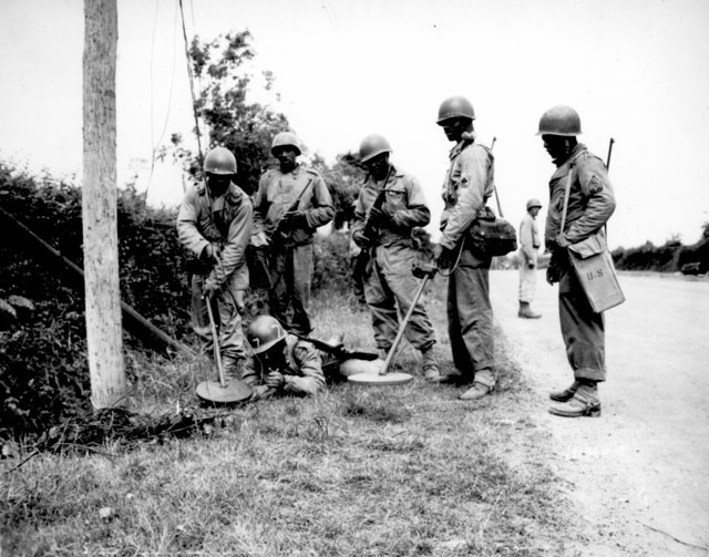 This mine detector crew is demonstrating what they do before going to work on or around telephone poles in France. Left to right: M/Sgt. Bennie Burns, Sgt. Vincent MacNeill, Sgt. Frank Mack, Pfc. Riggles McCutcheon, T/Sgt. John A. Barbee,  and Sgt. Thomas G. Alexander. July 13, 1944. Norton. 111-SC-191360-S.