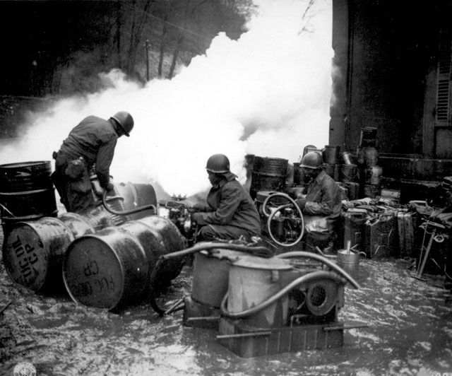 Soldiers of the 161st Chemical Smoke Generating Company, U.S. Third Army, move a barrel of oil in preparation to refilling an M-2 smoke generator, which spews forth a heavy cloud of white smoke. These men are engaged in laying a smoke screen to cover bridge building activities across the Saar River near Wallerfangen, Germany. December 11, 1944. Rothenberger. 111-SC-197552.