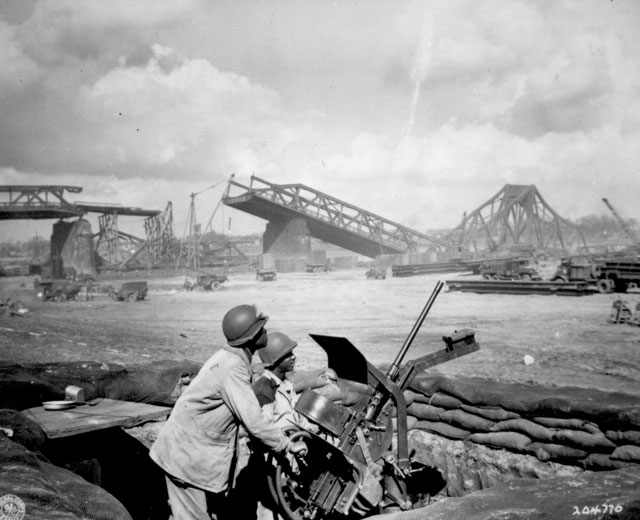 Pvts. George Cofield and Howard J. Davis guard a newly-constructed bridge site over the Rhine River, built by U.S. Ninth Army Engineers. March 30, 1945. T/5 H. R. Weber and Pfc. Sperry. 111-SC-204770.