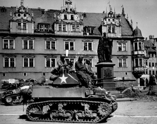 Crews of U.S. light tanks stand by awaiting call to clean out scattered Nazi machine gun nests in Coburg, Germany. April 25, 1945. 208-AA-32P-10.