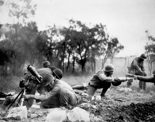Members of a Negro mortar company of the 92nd Division pass the ammunition and heave it over at the Germans in an almost endless stream near Massa, Italy. This company is credited with liquidating several machine gun nests  ca. November 1944. Acme. 208-AA-47U-6.