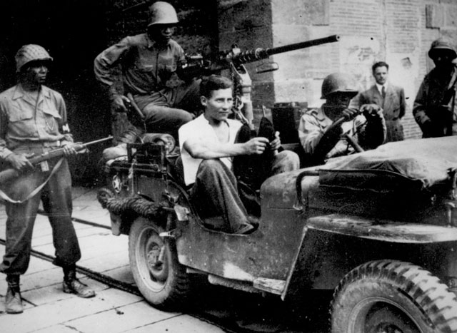 Tricky Nazi captured. German prisoner wearing civilian clothes, sits in jeep at south gate of walled city of Lucca, Italy, awaiting removal to a rear area. Ca. September 1944. 208-AA-305A-2
