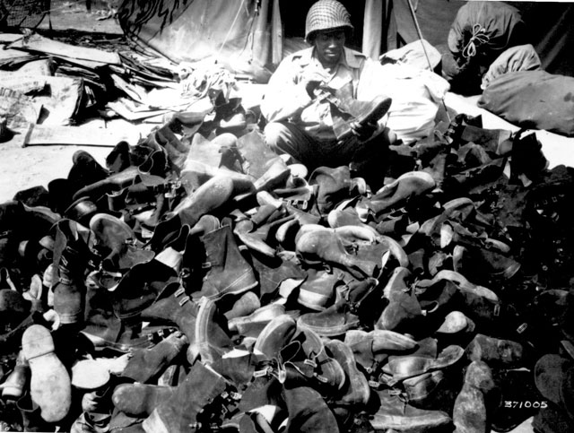 Pfc. Robert Askew with the 3278th Quartermaster Company, examines overshoes which have been turned in. Overshoes proved their worth and helped prevent trench foot during the rains. April 8, 1944. Lapidus. 111-SC-371005.