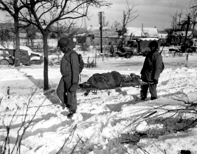 Body of American soldier is borne on stretcher from terrain in vicinity of Malmedy, Belgium, where on or about 17 December 1944, the Germans committed many atrocities. ca. December 1944. Taylor. 153-WC-1-19.