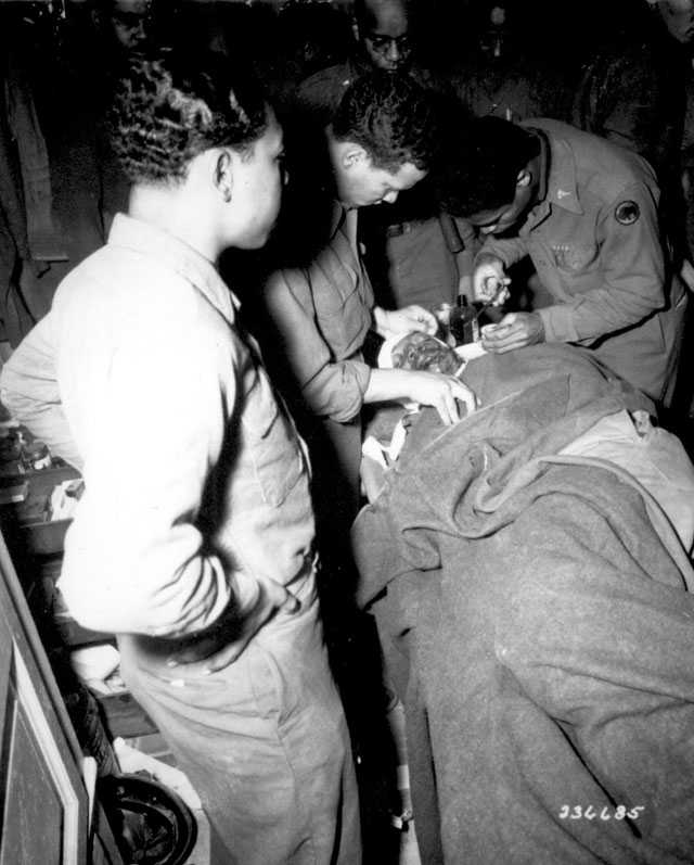 Capt. Ezekia Smith, 370th Inf. Regt., 92nd Div., receives treatment at the 317th Collecting Station, for shell  fragments in face and shoulders suffered near Querceta, Italy. Here, surgeon stitches the wound.  Fifth Army, Pietrasanta Area, Italy. February 10, 1945. Bull. 111-SC-236685