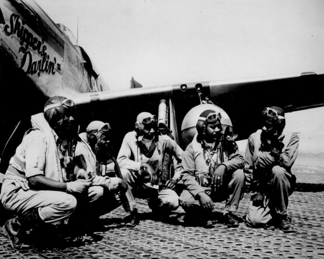 Fliers of a P-51 Mustang Group of the 15th Air Force in Italy 'shoot the breeze' in the shadow of one of the Mustangs they fly. Left to right: Lt. Dempsey W. Morgan, Jr.; Lt. Car roll S. Woods; Lt. Robert H. Nelson, Jr.; Capt. Andrew D. Turner; and Lt. Clarence P. Lester. Ca. August 1944. 208-NP-6XXX-1.