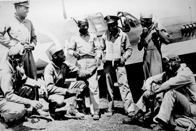 Pilots of a U.S. Army Air Forces fighter squadron, credited with shooting down 8 of the 28 German  planes destroyed in dog-fights over the new Allied beachheads south of Rome, on Jan. 27, talk over the day's exploits at a U.S. base in the Mediterranean theater. Negro members of this squadron, veterans of the North African and Sicilian campaigns, were formerly classmates at a university in the southern U.S. February 1944. 208-MO-18H-22051.