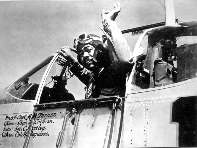 [Capt. Andrew D. Turner], who in a few minutes will be escorting heavy bombers en route to enemy targets, signals to the chief of his ground crew before taking off from a base in Italy. He is a member of the 15th U.S. Army Air Force, which has been smashing enemy objectives in Germany and the Balkans with both fighter and bomber craft. The pilot's plane, a Mustang, is named for a type of wild horse that once roamed in America. ca. September 1944. 208-MO-18K-32981.