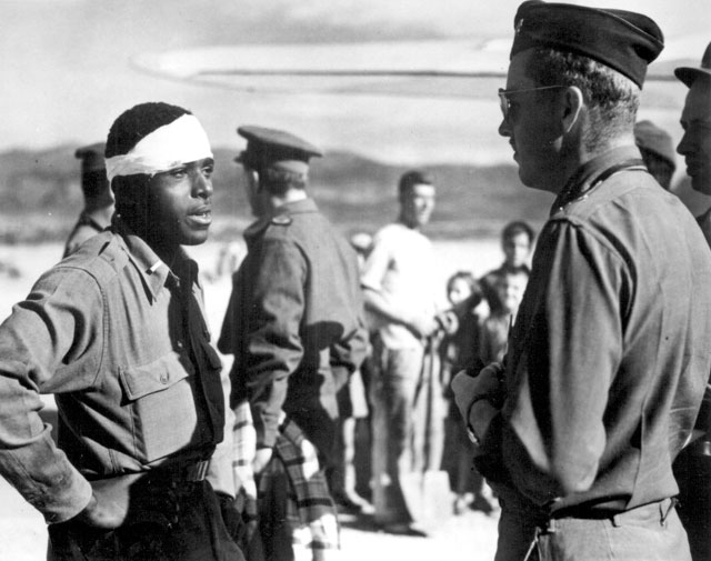 Lt. Andrew D. Marshall, pilot in a Negro fighter group of the Mediterranean Allied Air Force had his plane shot up by flak during a strafing mission over Greece before the Allied invasion. When he came down all that was left of the plane was his engine and himself. But he only suffered some bruises and cuts. Greeks hid him from the Nazis, then directed him to the British forces when they parachuted into Greece. Here Lt. Marshall tells an American pilot of the 51st Troop Carrier Wing of his harrowing experience. ca. October 1944. 208-AA-102E-5.
