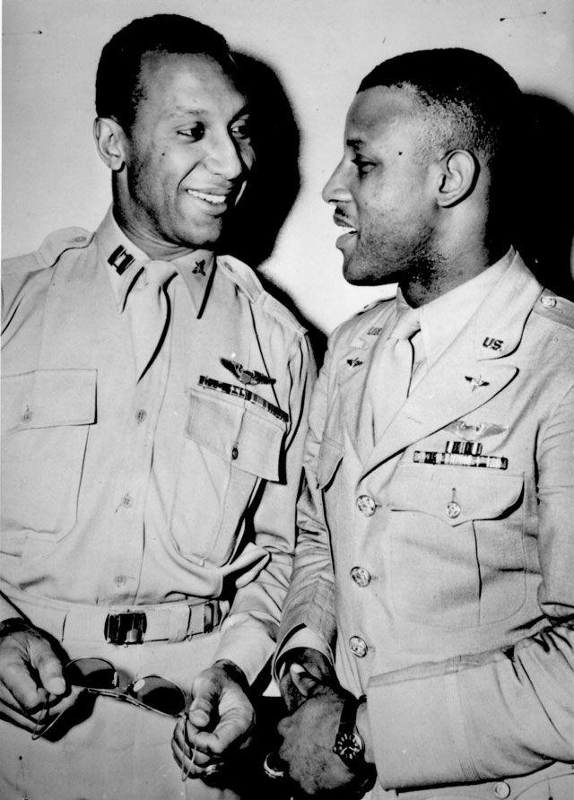Capts. Lemuel R. Custis (left) and Charles B. Hall, of the 99th Fighter Squadron of the U.S. Army Air Forces, chat while on leave in New York City. Their all-Negro squadron first went into action in North Africa on June 4, 1943, and is now closely supporting Allied ground forces advancing in Italy. The fighter group flies all types of combat missions--bomber escort, dive bombing, patrol for beachheads, and strafing. In one year, the squadron has made more than 3,000 sorties and has shot down 17 planes, scored 3 probables and damaged 6 other planes. Ca. June 1944. 208-MO-120H-29054.