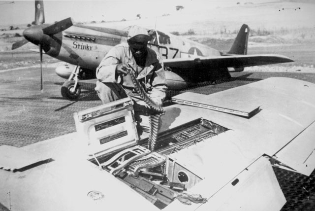 An armorer of the 15th U.S. Air Force checks ammunition belts of the .50 caliber machine guns in the wings of a P-51 Mustang fighter plane before it leaves an Italian base for a mission against German military targets. The 15th Air Force was organized for long range assault missions and its fighters and bombers range over enemy targets in occupied and satellite nations, as well as Germany itself. Ca. September 1944. 208-MO-18H-32984.