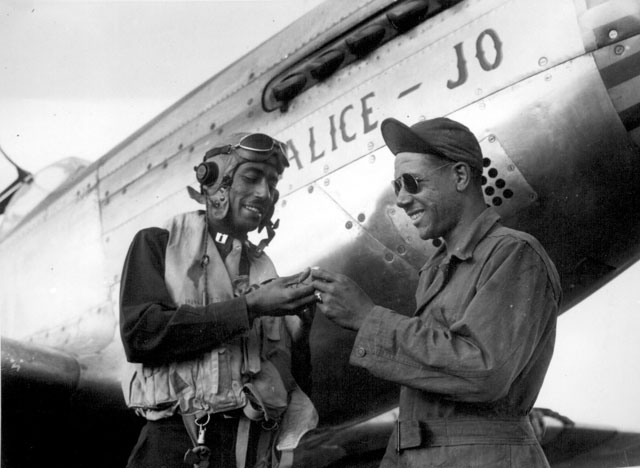 Capt. Wendell O. Pruitt., one of the leading pilots of the 15th Air Force always makes sure that he leaves his valuable ring with his crew chief, S/Sgt. Samuel W. Jacobs. Ca. November 1944. 208-AA-46BB-4.