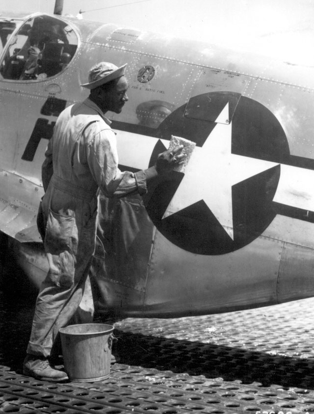 Staff Sgt. William Accoo, crew chief in a Negro group of the 15th U.S. Air Force, washes down the P-51 Mustang fighter plane of his pilot with soap and water before waxing it to give it more speed. Ca. September 1944. 208-AA-46BB-30.