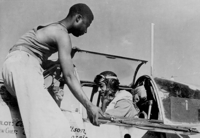 Staff Sgt. Alfred D. Norris crew chief of a Negro fighter group of the 15th U.S. Air Force, closes the canopy of a P-51 Mustang for his pilot, Capt. William T. Mattison operations officer of the squadron based in Italy. N.d. 208-AA-46BB-6.
