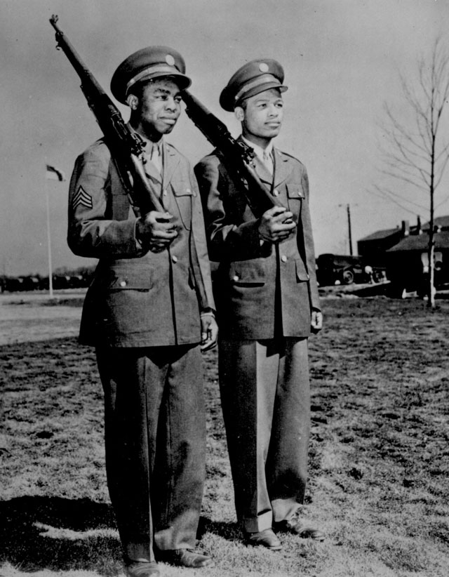 Jackie Wilson (left) and Ray Robinson have fought two bitterly contested ring encounters. Now it's Sgt. Wilson and Pvt. Robinson in the same Aviation Squadron at Mitchel Field, New York, and they stand shoulder to shoulder--ready for a fight to the death on the Axis. 1943. 208-PU-214B-5.