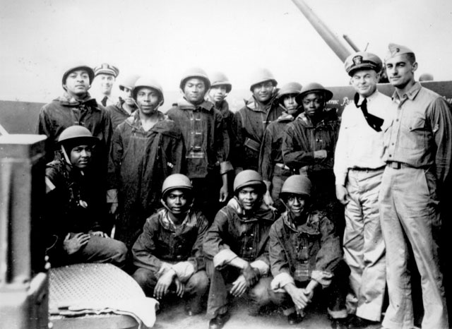 Negro messmen aboard a United States Navy cruiser who volunteered for additional duty as gunners. They have been doing proficient work under battle conditions on a task force in the Pacific under the instruction of the officers at the right. July 10, 1942. 80-G-21743
