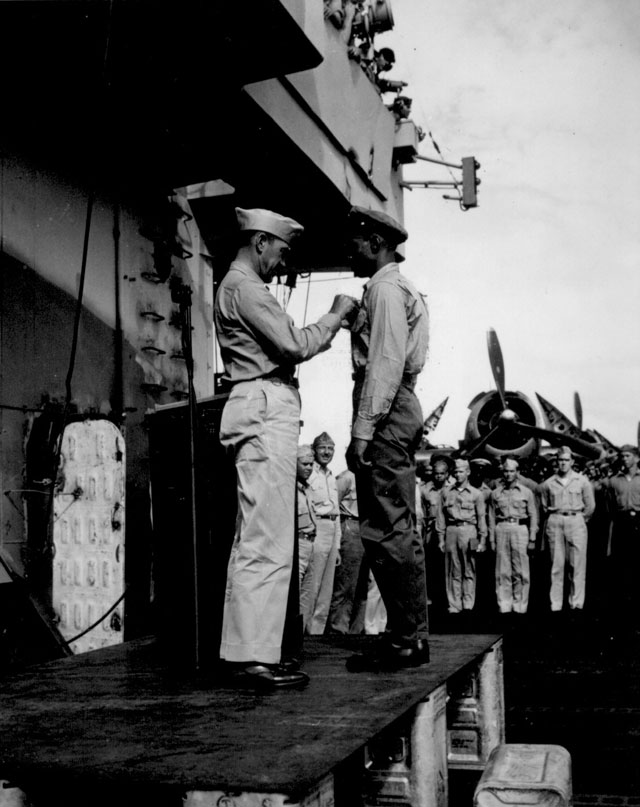 Capt. H. W. Taylor making award presentations aboard U.S.S. Cowpens (CVL 25). Fred Magee, Jr., St3/c USN, receiving commendation of the Secretary of the Navy. The commendation was for attempting to rescue, at a risk to his own life, a shipmate from drowning. October 1944. 80-G-291220