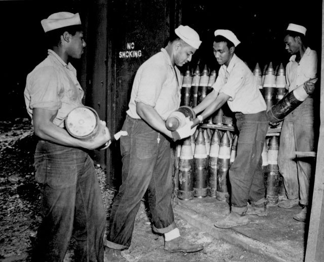 Enlisted men serving on Espiritu Santo in the New Hebrides placing 6-inch shells in magazines at the Naval Ammunition Depot. From left to right: S1/c Dodson B. Samples, S1/c Raymond Wynn, S1/c Edward L. Clavo, and S1/c Jesse Davis. N.d. 80-G-123941