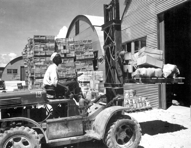 M. D. Shore, S1/c, operating a forklift truck at the Navy supply depot at Guam, Marianas. June 8, 1945. 80-G-330221
