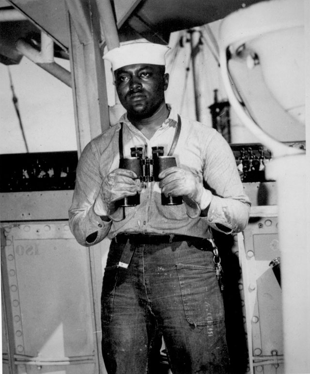 Looking to sea from the signal bridge is Napoleon Reid, Seaman 2/c., USNR, shown standing on lookout watch on a ship somewhere in the Pacific. March 19, 1945. 208-NP-7III-1.