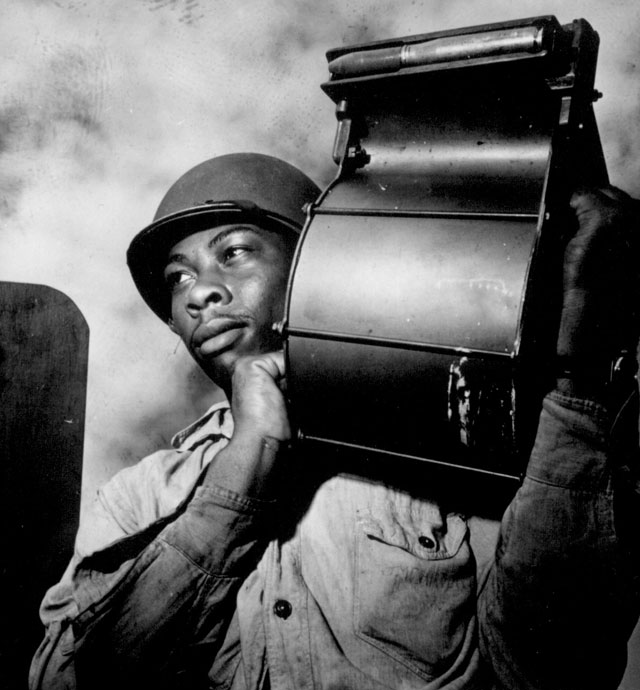 Crewmen aboard U.S.S. Tulagi (CVE-72) en route to southern France for Aug. 15th invasion. Miles Davis King, StM 2/c, carrying a loaded magazine to his 20mm gun. August 1944. 80-G-417623