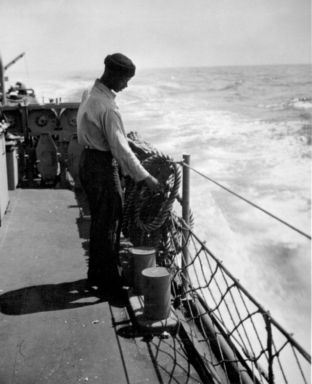 A deck hand loops a manila line. N.d. 208-NP-7QQ-5.