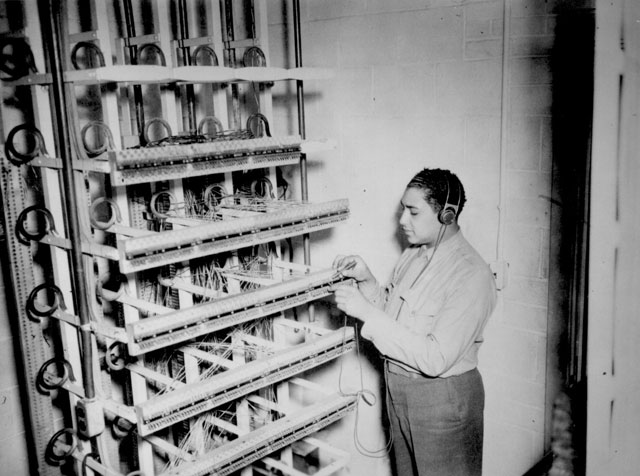 Marine Cpl. Robert L. Hardin checks the main distributing frame in Montford Point's headquarters for line difficulties. N.d. Sgt. L. A. Wilson. 127-N-8768.