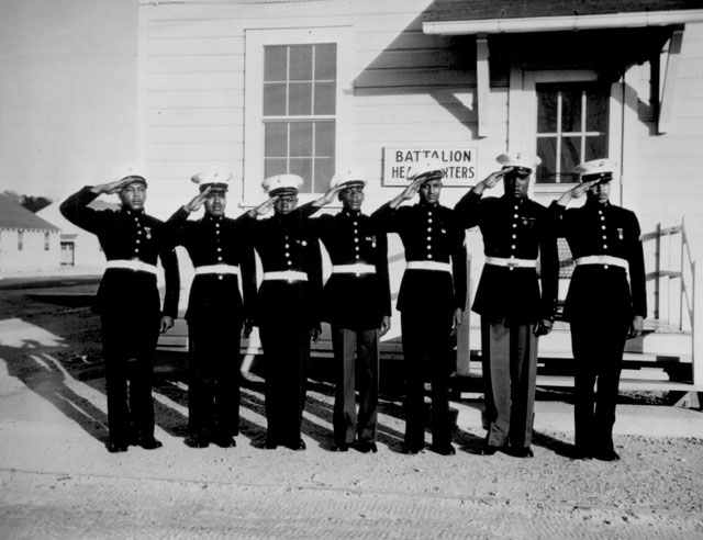 Although a dress uniform is not a part of the regular equipment, most of the Negro Marines spend $54 out of their pay for what is generally considered the snappiest uniform in the armed services. Photo shows a group of the Negro volunteers in their dress uniforms. Ca. May 1943. Roger Smith. 208-NP-10NN-2.