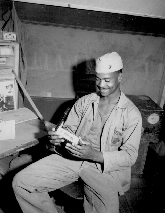 Pfc. Luther Woodward , a member of the Fourth Ammunition Company, admires the Bronze Star awarded to him for his bravery, initiative and battle-cunning.  The award was later upgraded to the Silver Star. April 17, 1945. Cpl. Irving Deutch. 127-N-119492.
