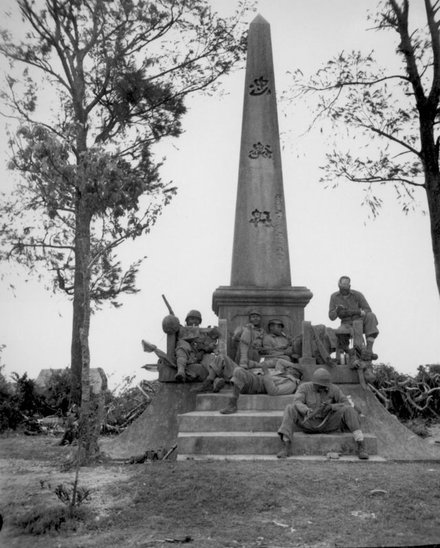 Marines, following the rapid Japanese retreat northward on Okinawa, pause for a moments rest at the base of a Japanese war memorial. They are (on steps) Pfc. F. O. Snowden; Navy Pharmacist's Mate, 2nd class R. Martin; (on monument, left to right) Pvt. J. T. Walton, Pvt. R. T. Ellenberg, Pfc. Clyde Brown, Pvt. Robb Brawner. Photo was taken during the battle for Okinawa. April 12, 1945. Cpl. Art Sarno. 127-N-117624