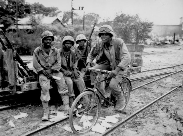 Negro Marines, attached to the Third Ammunition Company, take time out from supplying ammunition to the front line on Saipan. Riding captured bicycle is Pfc. Horace Boykin; and left to right, Cpl. Willis T. Anthony, Pfc. Emmitt Shackelford, and Pfc. Eugene Purdy. June 1944. 127-N-8600.
