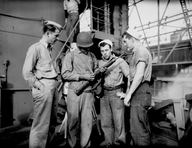 Aboard a Coast Guard-manned transport, a Negro Marine, Robert Stockman, goes over his carbine with Coast Guardsmen. Ca. February 1944. 26-G-321