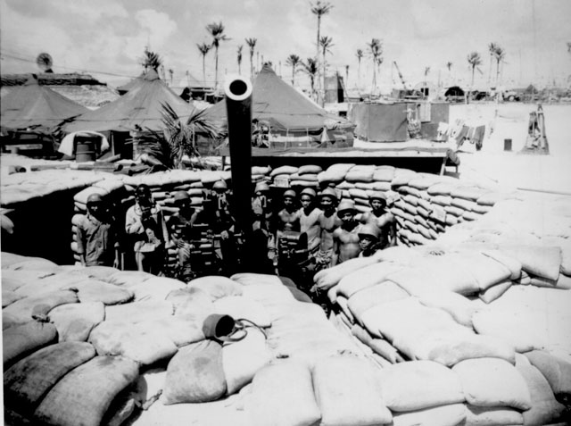 Surrounded by a veteran crew of Marines who have spent 15 months in the Southwest and Central Pacific, this gun, named the 'Lena Horne' by its crew, points majestically skyward. The gun is manned by members of [the 51st] Defense Battalion, one of two such Negro units in the Corps. 1945. Nicholson. 127-N-12174.